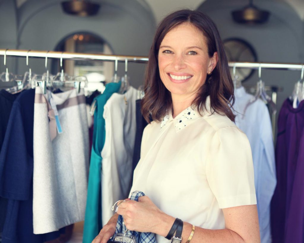 TITLE Heather Rosenfield, perfectly polished in our Clementine Embellished Short Sleeve Collared Shirt and SKIRT, merchandises the racks.